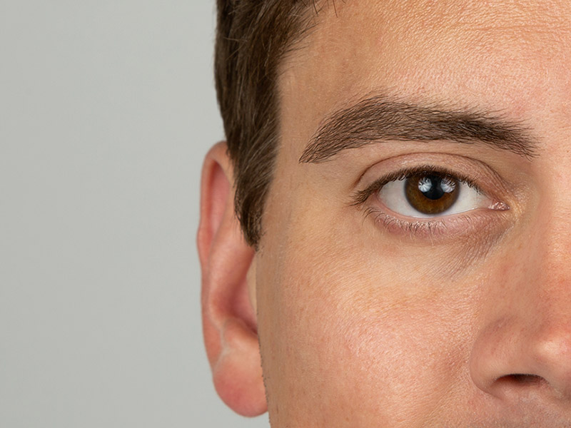 closeup of mans face showing groomed eyebrow