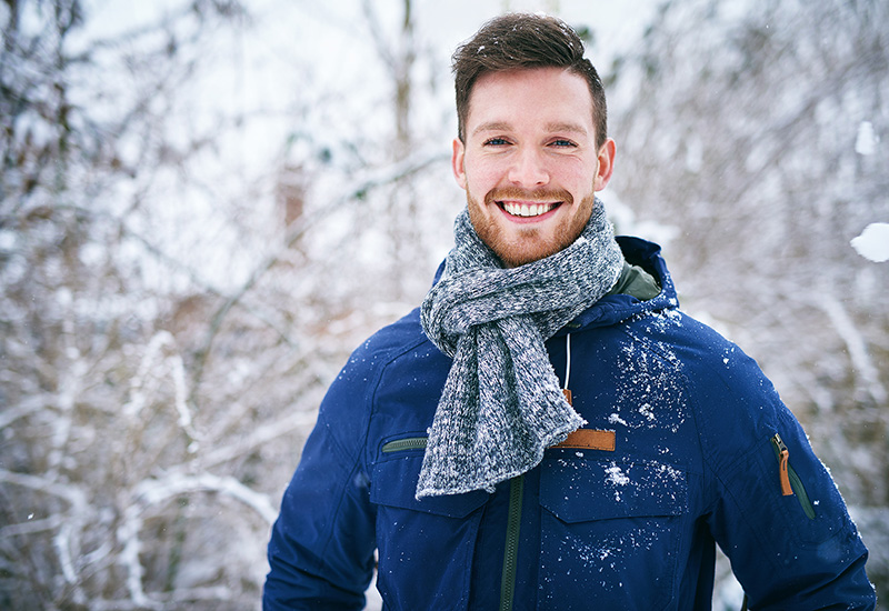 Man smiling outside in the snow
