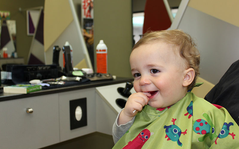 Kid smiling after his haircut