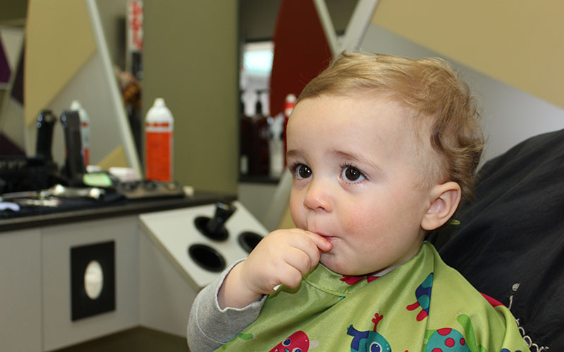 Kid sitting in the salon chair with a lollipop