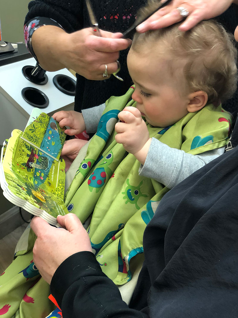 Kid reading a picture book during his haircut