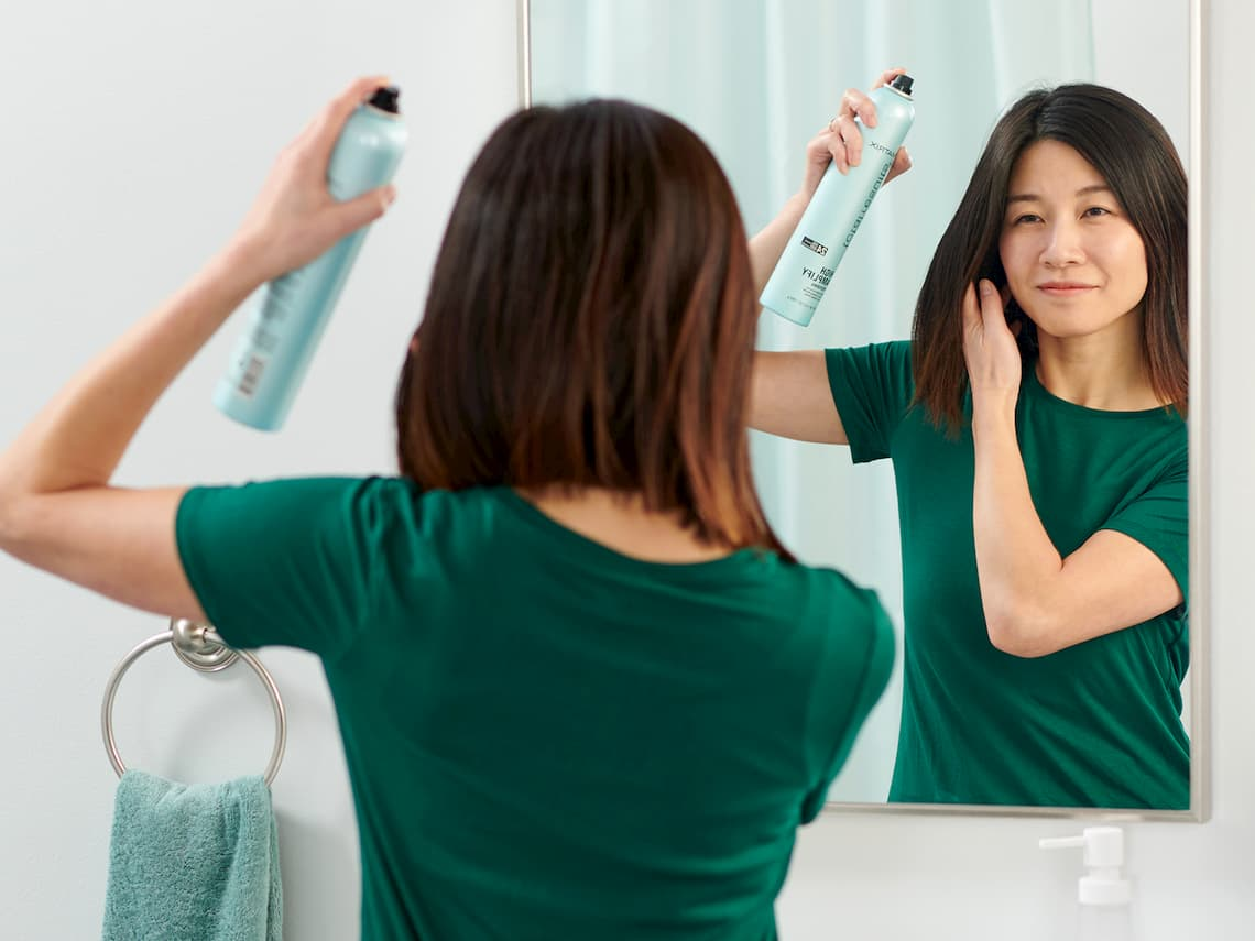 woman using hairspray in front of a mirror
