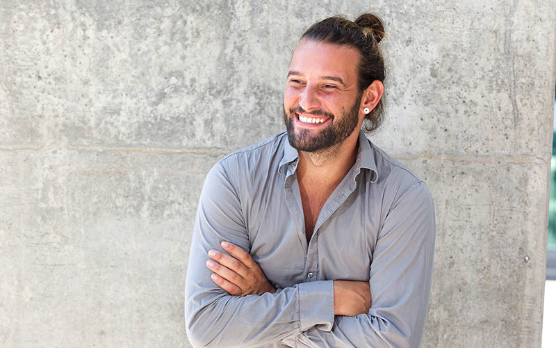Smiling man with bun hairstyle