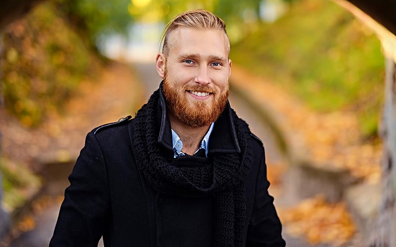 Portrait of smiling redhead male in an autumn park.