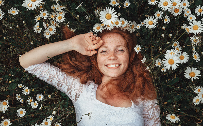 Woman laying in a field of daisies