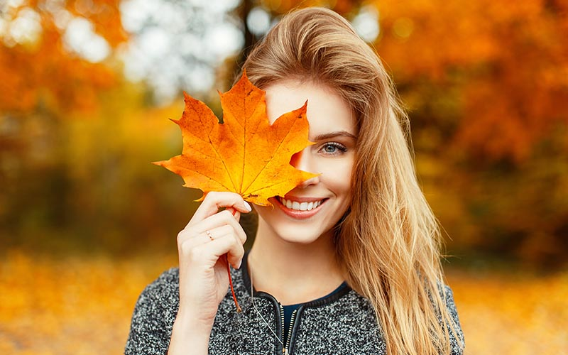 Smiling woman in front of fall foliage